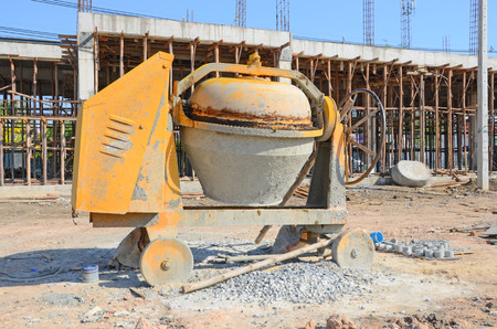 Old yellow mortar mixer in front of construction site