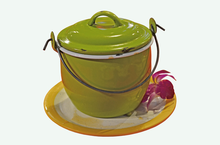 Green iron pot with lid and handle on white tray