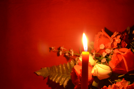 Candle light and roses on red background