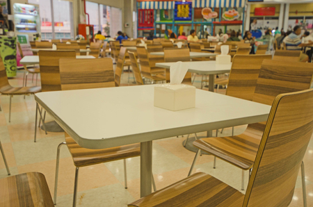 Un poco de cliente y sillas vacías en la tienda de alimentos.
