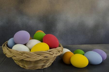 Rainbow color of egg in rattan basket and on the floor