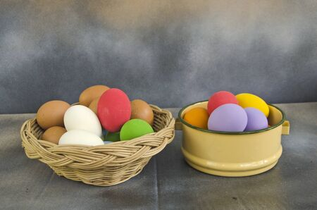 Basket and bowl of colored eggs on the floor