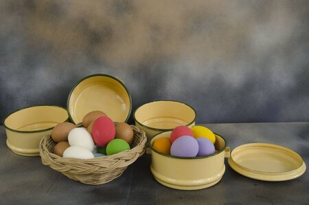 Colored eggs in basket and bowl beside the wall