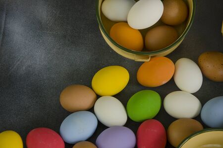 Colored eggs on the floor and in the bowl