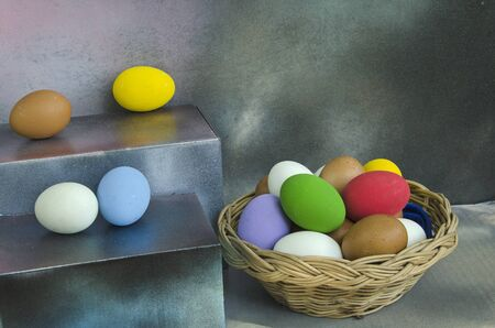 Colored eggs in basket and on shelf
