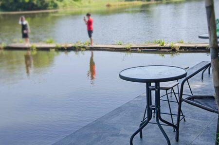 Black patio furniture on concrete shore beside river