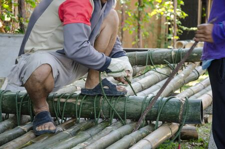 Men make raft by using bamboos and ropes
