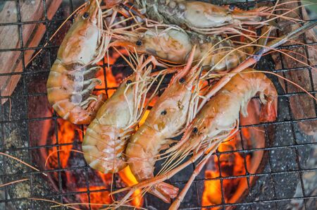 Yummy grilled prawns on hot fire in stove Фото со стока