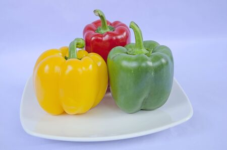 Three bell pepper in ceramic dish on blue background Imagens