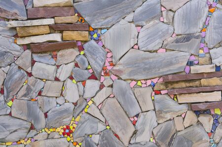 Beautiful colored ceramic pieces and  flagstone wall 写真素材