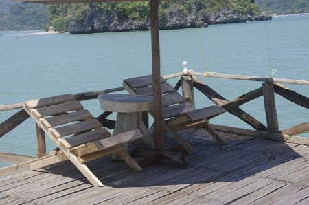 Wooden seats and table on terrace in the sea