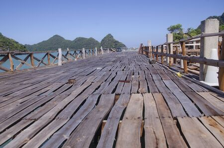 Long wooden terrace with fence in the sea