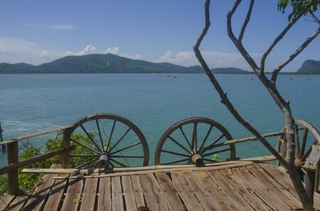 Wooden terrace with wagon wheel fence over blue sea