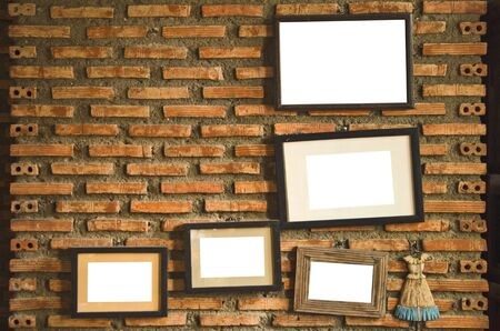 Old blank frame with white background on brick wall