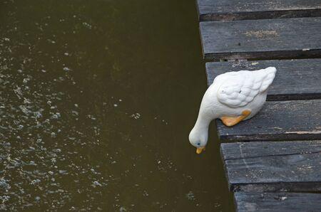 Watching duck sculpture on old wooden bridge