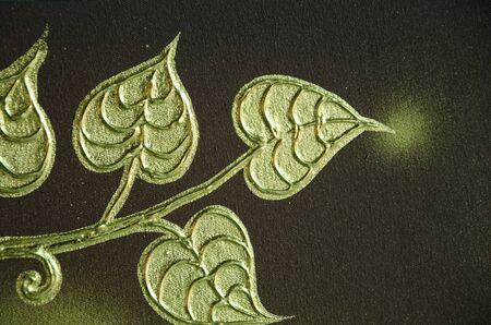 Art of golden Bodhi leaves on dark brown floor Banco de Imagens