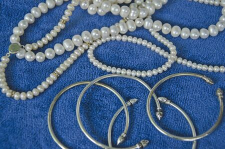 Top view of pearl necklaces and bracelets on blue clothes