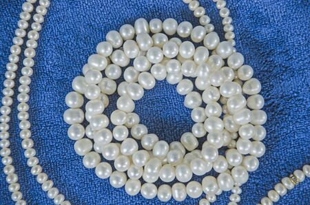 Top view of white pearl necklaces on blue floor Banco de Imagens