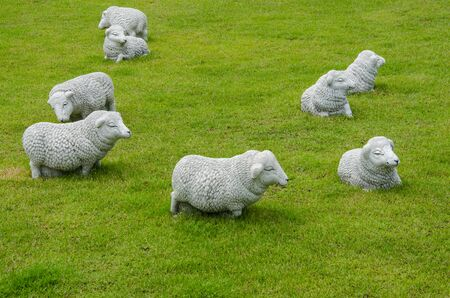 Beautiful white sheep sculptures in green lawn
