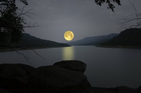 Romantic full moon over the river in the mountains 写真素材