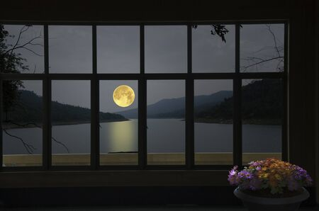 Beautiful full moon over the river in window view