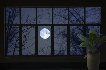 White moon in blue sky in glass window view at night