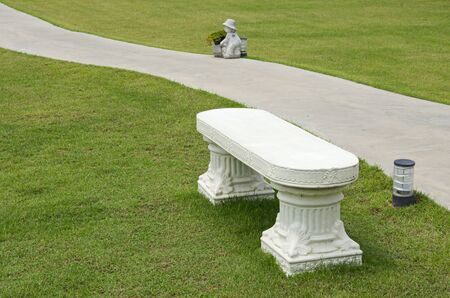 White seat and concrete pathway in green lawn