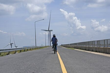 Riding woman along the road to wind turbine
