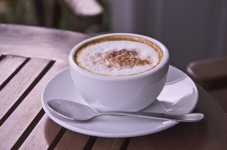 White ceramic cup of coffee and small dish on brown floor