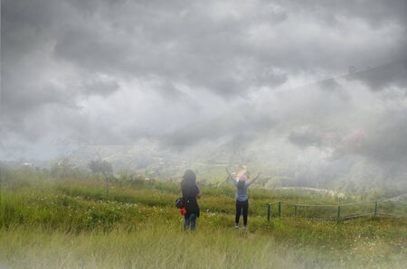 Tourists on green grass hill with thick fog Imagens