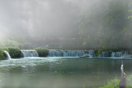 Beautiful waterfall on small cliff with thick fog in the park