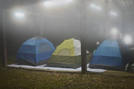 Sleeping tents in electric lights with fog in the night
