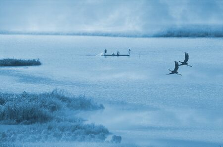 Couple canes over the river with fishermen in the fog Imagens
