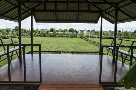 Brown smooth wooden floor with seats of pavilion in the field Imagens