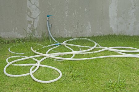 Long white rubber band for on green lawn wit faucet on concrete wall Imagens