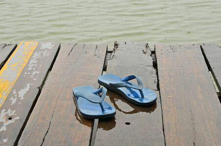 Old blue sandals on wooden floor in rain
