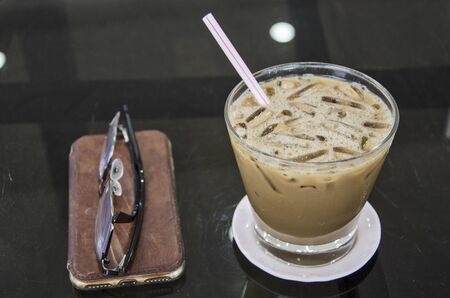 Iced coffee in glass with saucer on black floor of table Imagens