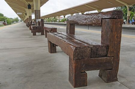 Waiting wooden seats for passengers at train station Imagens