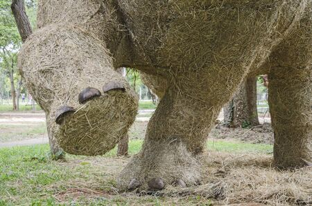 Big feet of elephant sculptured straw puppet in park