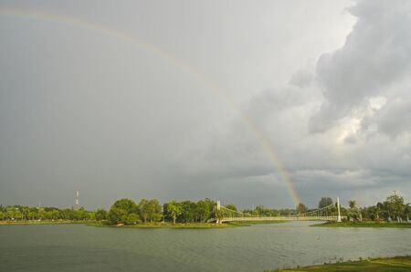 Beautiful rainbow and bit of rain  in the sky over the lake Imagens