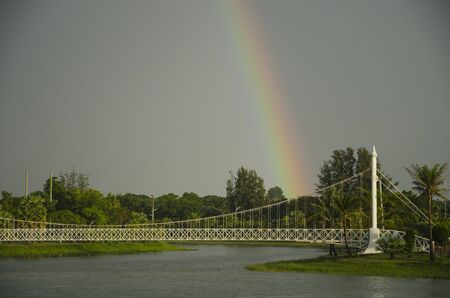 Beautiful rainbow over green trees and withe bridge in the park Imagens