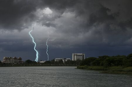 Scared lighting with hard rains over the town beside the lake Imagens