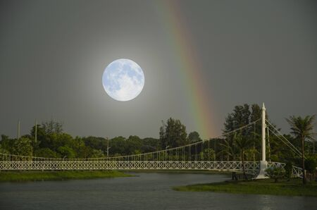 Big white moon and rainbow over the park in early evening
