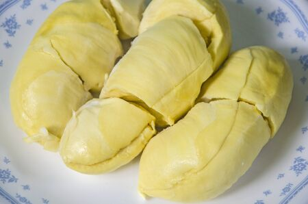 Yummy yellow aril of durian fruit in white dish close up