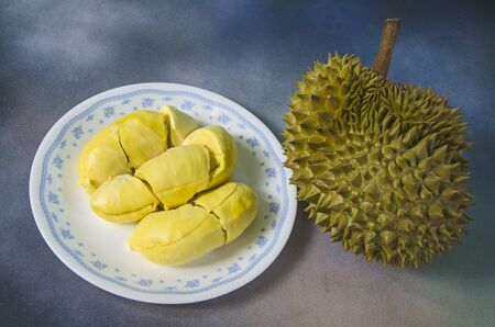 Yummy yellow aril of durian in white dish and fruit