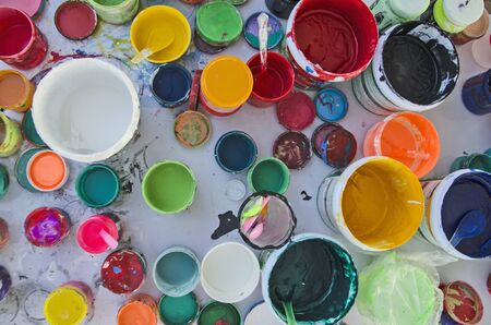 Bottles and buckets of acrylic colors with lids on white floor Imagens
