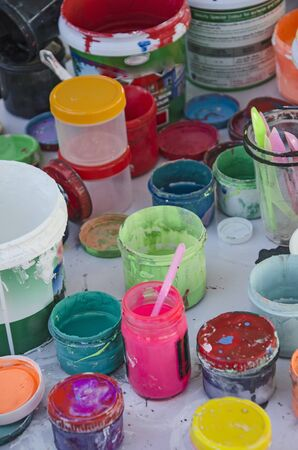 Bottles and buckets of many acrylic colors on the floor Imagens