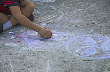 Young street artist with chalk painted workmanship
