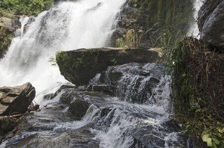 Big stone in beautiful waterfall on rock cliff