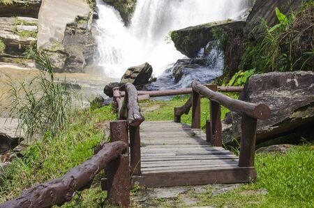 Brown wooden bridge to beautiful white waterfall